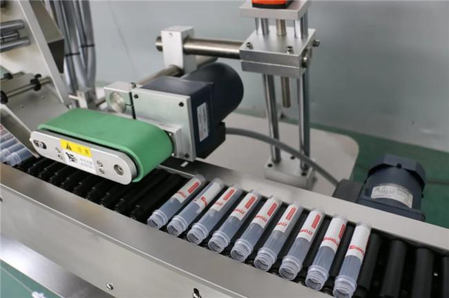 Automatikus vízszintes tekercselés a fecskendő öntapadó matrica címkéző gép körül
